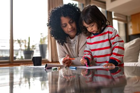 Loving mother and her adorable little girl coloring at home
