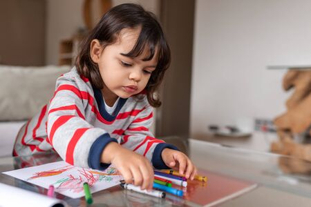 Adorable little girl coloring with crayons at home Stockfoto