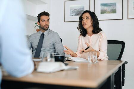 Young businesswoman explaining ideas to coworkers during an office meeting Stock Photo