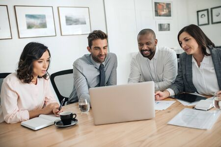 Diverse businesspeople smiling while working together on a laptop