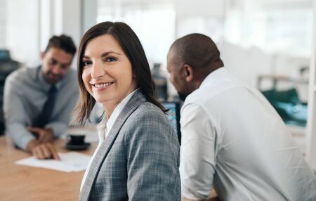 Smiling businesswoman sitting in an office meeting with colleagues Stock Photo