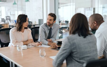 Diverse group of businesspeople talking together during an office meeting