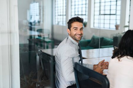 Smiling young businessman sitting with colleagues in a boardroom Stock Photo
