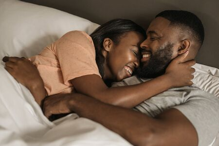 Affectionate young African American couple hugging each other in bed Banque d'images - 130068262