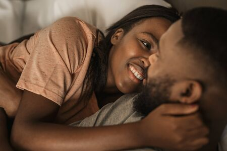 Affectioante young African American couple lying together in bed Banque d'images - 130068263