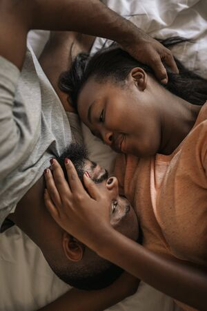 African American couple looking into each others eyes in bed Stockfoto