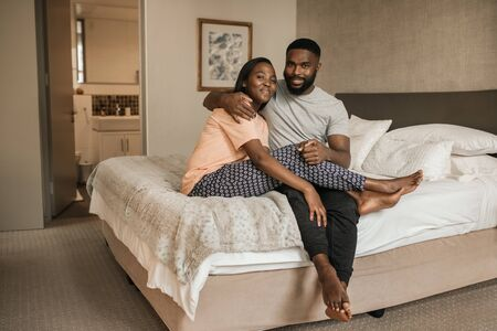 Smiling young African American couple sitting together on their bed 写真素材