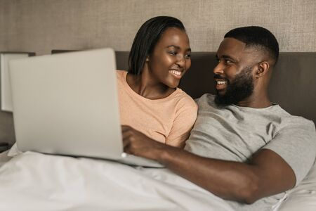 Smiling African American couple using a digital tablet in bed