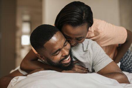 Lachendes junges afroamerikanisches Paar, das zusammen im Bett spielt