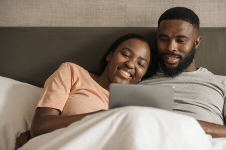 Young African American couple using a digital tablet in bed