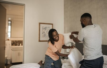 Laughing African American couple having a pillow fight in bed 写真素材