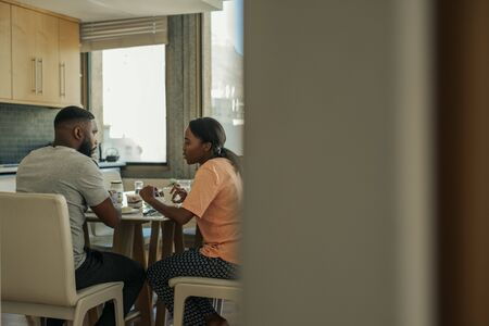 Young African American couple talking together over breakfast Stock Photo