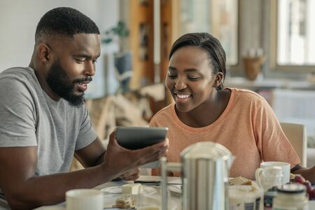 Smiling African American couple eating breakfast and using a tablet