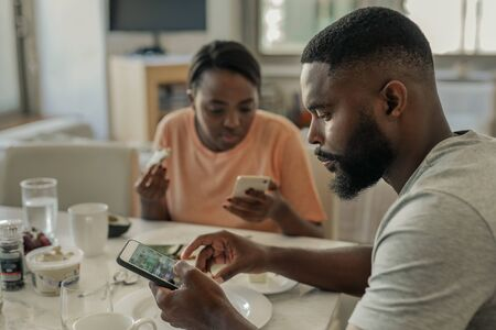 Young African American couple distracted from breakfast by their cellphones