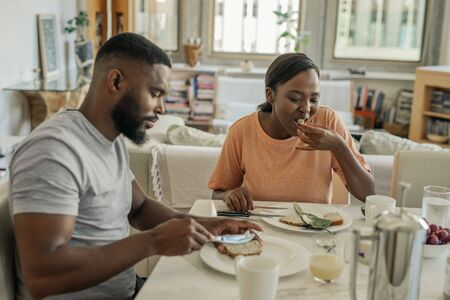 Young African American couple sitting at home eating breakfast