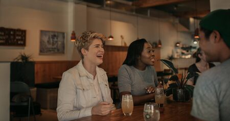 Young woman laughing with her friends in a bar