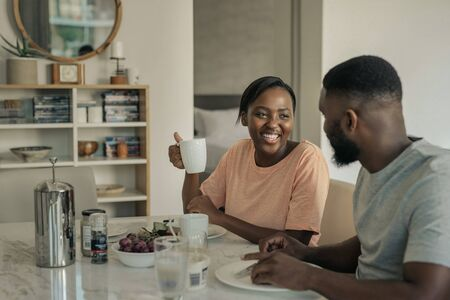 Laughing young African American couple enjoying breakfast together at home Stock Photo