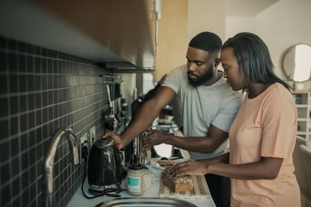 Young African American couple preparing breakfast in their kitchen