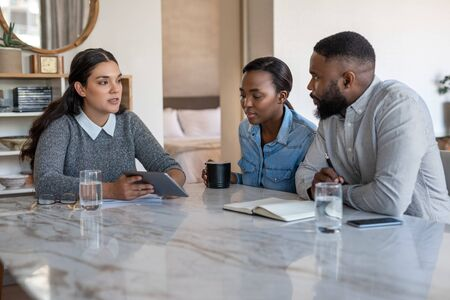 Financial advisor talking with an African American couple at home