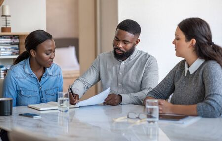 African American couple signing documents with their financial planner