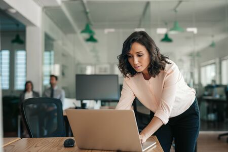Businesswoman leaning over her office desk working on a laptop