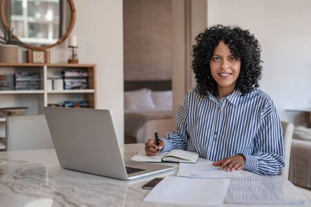 Smiling young female entrepreneur working from home on a laptop