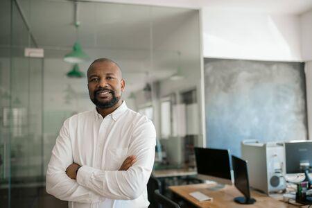 Homme d'affaires afro-américain souriant, seul dans un grand bureau