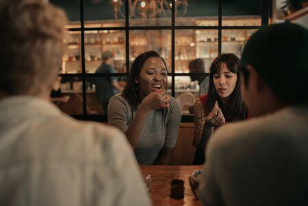 Vrienden die 's avonds lachen tijdens het diner in een bistro Stockfoto