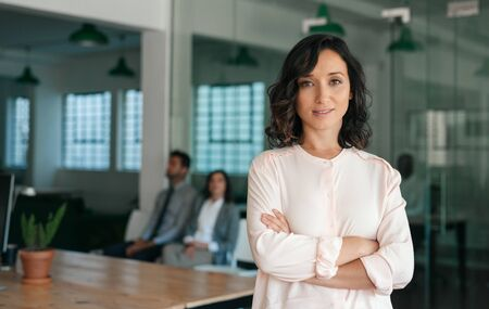 Smiling young businesswoman standing confidently in a large office Stock fotó
