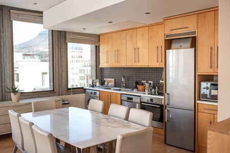 Interior de la cocina de un pequeño apartamento con mesa de comedor, sillas y diversos electrodomésticos. Foto de archivo