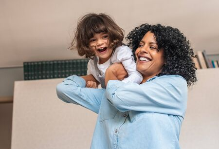 Laughing mom and cute little daughter playing at home