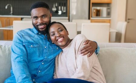 Affectionate young African American couple sitting together on their sofa Stock fotó