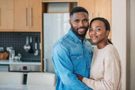 African American couple standing in each others arms at home