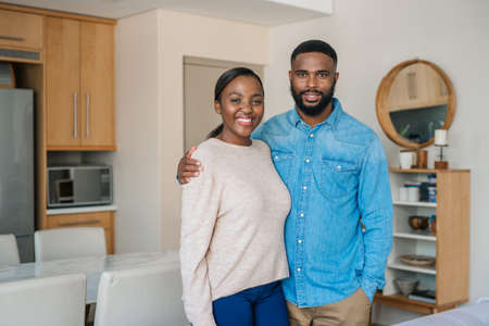 Portrait of a young African American couple smiling while standing together in their stylish modern apartment Stok Fotoğraf