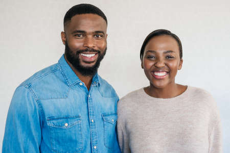 Portrait of a content young African American couple smiling while standing side by side together in their apartment
