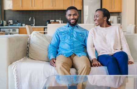 Portrait of a smiling young African american couple relaxing together on their sofa in their living room at home