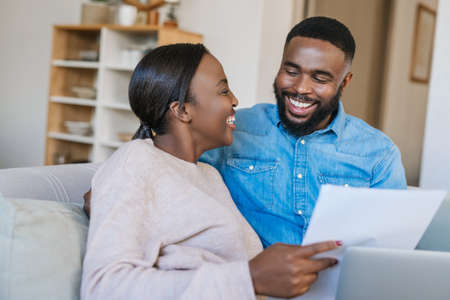 Laughing young African American couple sitting on their living room sofa together at home paying bills online with a laptop Stok Fotoğraf