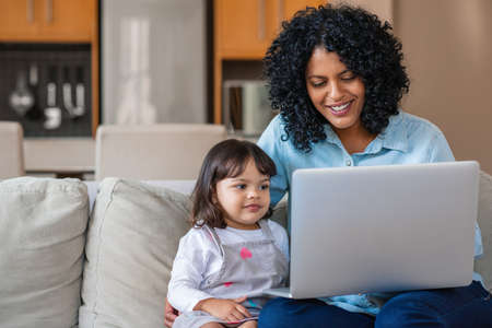 Smiling mother and her cute little daughter watching something together on a laptop while sitting on their living room sofa