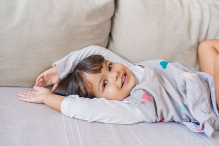 Portrait of a cute little girl smiling while playing on a sofa in her living room at home Stok Fotoğraf