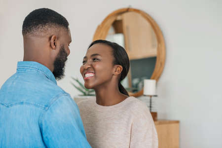 Young African American woman smiling and looking at her husband while standing arm in arm together in their modern apartment Stok Fotoğraf