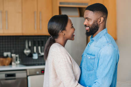 Young African American couple smiling and looking into each other's eyes while standing arm in arm together at home
