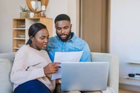 Young African American couple paying bills online with a laptop while sitting together on their living room sofa at home
