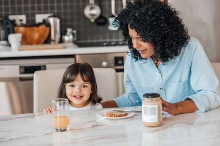 Cute little girl sitting with her smiling mom at their kitchen table making peanut butter sandwiches for a snack Stok Fotoğraf