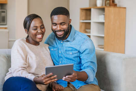Laughing young African American couple sitting together on their living room sofa streaming video online with a digital tablet Stok Fotoğraf