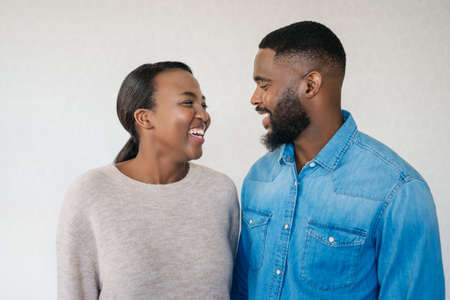 Smiling young African American couple looking at each other while standing arm in arm together in their modern apartment Stok Fotoğraf