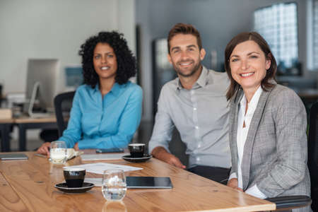 Portrait of a diverse group of smiling businesspeople sitting together at a table in an office before a meeting