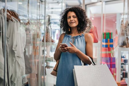 Smiling woman using her cellphone while out clothes shopping