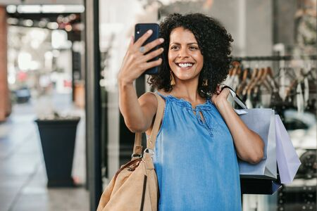 Smiling young woman taking a selfie while out clothes shopping