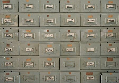 Large metal cabinet of drawers filled with an assortment of small parts inside of a woodworking shop