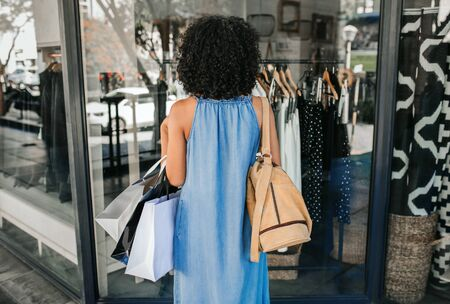 Rearview of a woman standing on a sidewalk and looking at the window display of a store while out clothes shopping Reklamní fotografie